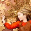Autumn fall little blond girl on dried tree leaves — Stock Photo