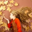 Autumn girl on dried leaves blowing wind lips — Stock Photo #8805310