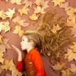 Autumn girl on dried leaves blowing wind lips — Stock Photo #8805451
