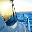 Blue golden sunrise sailing on boat side — Stock Photo