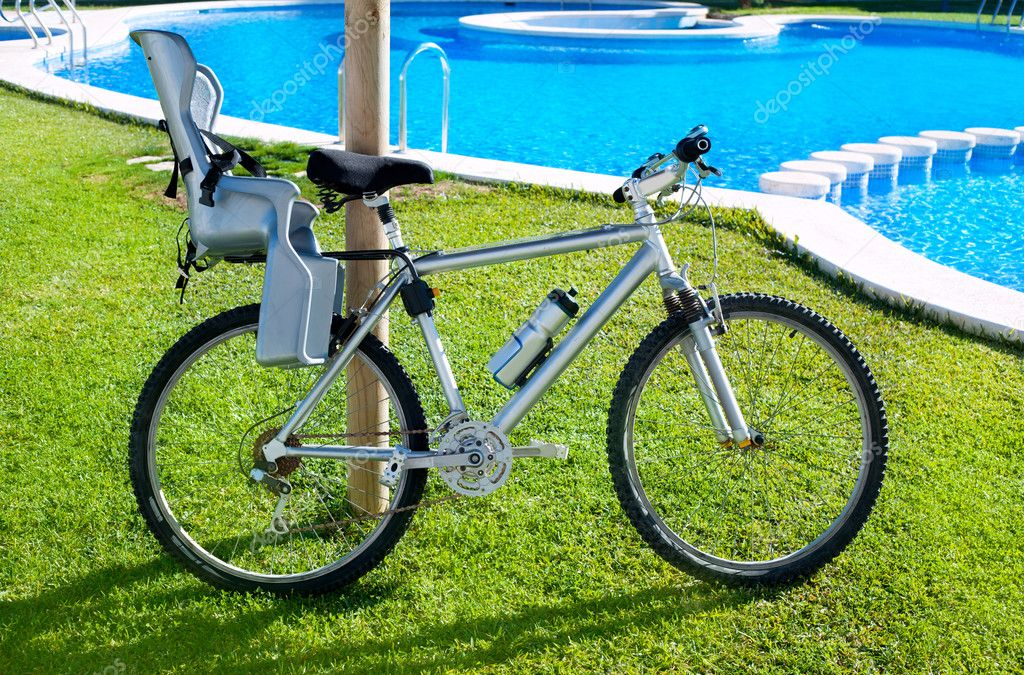 Bicycle with baby seat in grass pool outdoor on summer vacation — Stock Photo #8956917