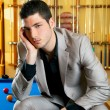Stock Photo: Handsome man with suit sitting in billiard pool