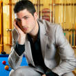 Handsome man with suit sitting in billiard pool — Stock Photo