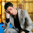 Stock Photo: Handsome mwith suit sitting in billiard pool
