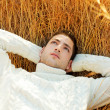 Autumn winter man portrait laying in golden grass — Stock Photo
