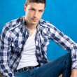 Handsome young man with plaid shirt sitting on wood — Stock Photo