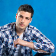 Handsome young man with plaid shirt on blue — Stock Photo #9857370