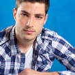 Handsome young man with plaid shirt on blue — Stock Photo #9857377