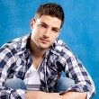 Handsome young man with plaid shirt on blue — Stock Photo #9857413