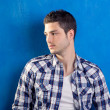 Handsome young man with plaid shirt on blue — Stok fotoğraf
