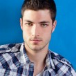 Handsome young man with plaid shirt on blue — Stock Photo #9857510