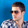 Handsome man with plaid shirt and sunglasses - Stock Photo