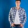 Stock Photo: Handsome young mwith plaid shirt denim jeans in blue