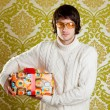 Retro hip young man glasses holding gift box — Stock Photo #9858208