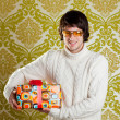 Retro hip young man glasses holding  gift box - Stock Photo