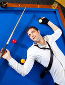 Billiard young man player lying on pool blue table — Stock Photo