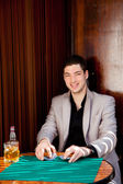Latin handsome gambler man in table playing poker — Stock Photo