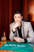 Latin handsome gambler man in table playing poker — Stock Photo