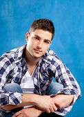 Handsome young man with plaid shirt on blue — Stock Photo