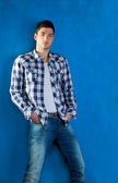 Handsome young man with plaid shirt denim jeans in blue — Stock Photo