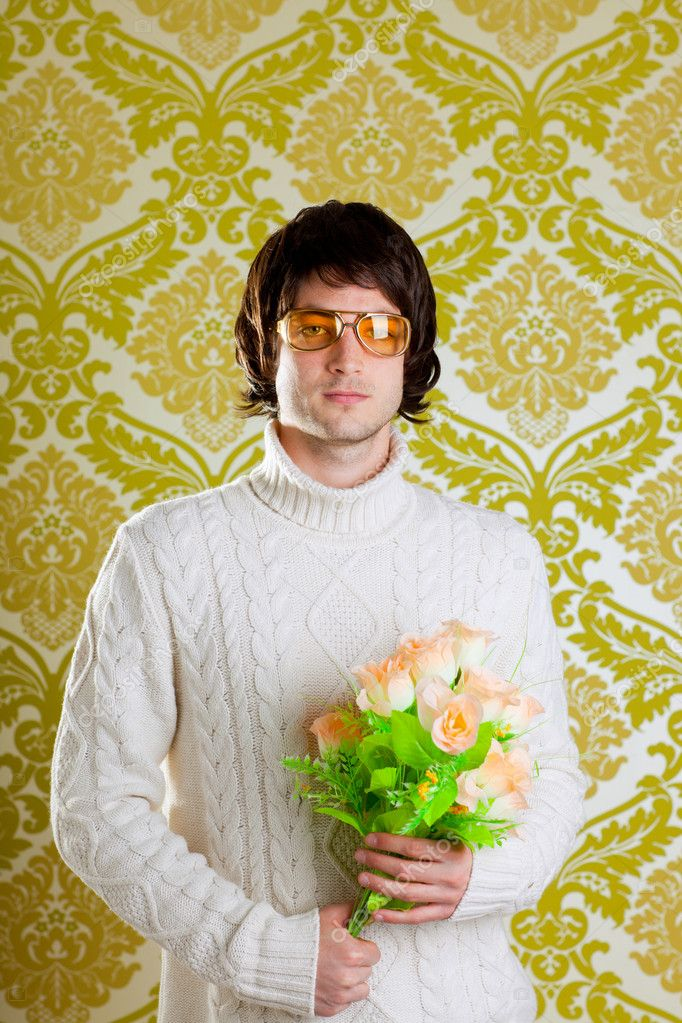 Retro hip young man vintage glasses holding valentines flowers bouquet on wallpaper — Stock Photo #9858148