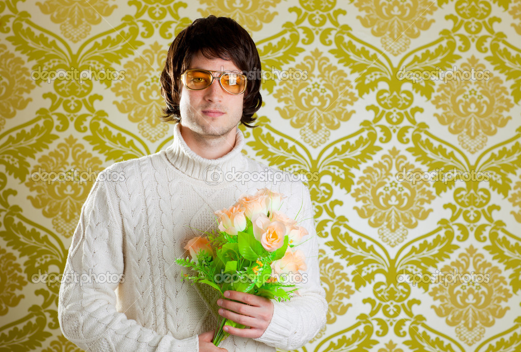 Retro hip young man vintage glasses holding valentines flowers bouquet on wallpaper — Stock Photo #9858176