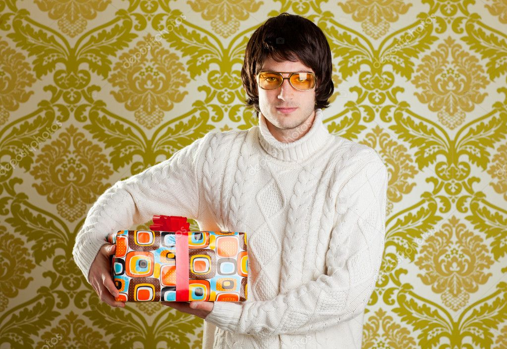 Retro hip young man glasses holding  psychedelic gift box on wallpaper  Stock Photo #9858208