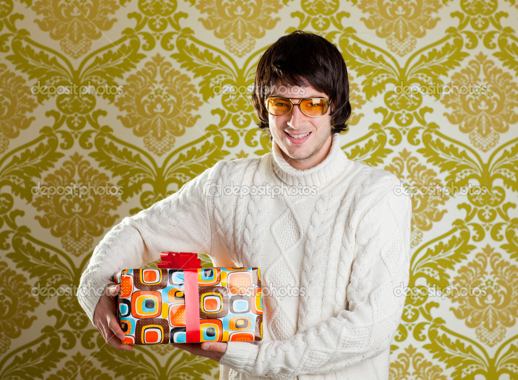Retro hip young man glasses holding  psychedelic gift box on wallpaper — Stock Photo #9858217
