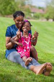 Adorable african mother with her daughter in the garden — Stock Photo