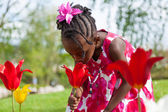 Cute little african american girl playing in the garden — Stock Photo