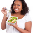 Young african american woman eating salad - Stock Photo