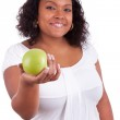 Young african american woman giving an green apple — Stock Photo