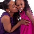 Happy african mother kissing her daughter — Stock Photo
