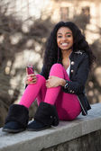 Portrait of a happy young african american teenage girl listenin — Stock Photo