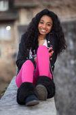 Portrait of a happy young african american teenage girl listenin — Stok fotoğraf
