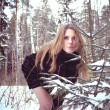 Beautiful young woman in winter forest — Stock Photo