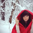 Red Hood Girl in a winter snow forest — Stock Photo