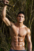 Male model with muscles on the countryside — Stock Photo