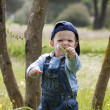 Young child with cap offers a flower - Stockfoto