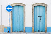 Two blue doors and blue traffic sign — Stock Photo