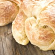 Close up of fresh croissants on a wooden surface - Stock Photo