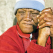 An old African woman with folded hands - focus on the weathered hands - Stock Photo