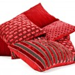 Red cushions stacked up on a white background - Stock Photo