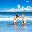 Beautiful young women playing on the beach — Stockfoto