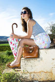 Young woman with handbag and umbrella sitting on old rustic stairs — Stock Photo