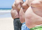 Close up of three obese fat men of the beach — Stock Photo