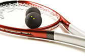 Close up of a red and silver squash racket and ball — Stock Photo
