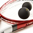Close up of a red and silver squash racket and ball on a white background with space for text — Stock Photo #10370172
