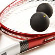 Close up of a red and silver squash racket and ball on a white background with space for text - Stock Photo