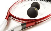Close up of a red and silver squash racket and ball on a white background with space for text — Stock Photo